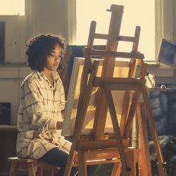 Woman in front of easel.