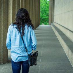 Woman walking alongside big wall